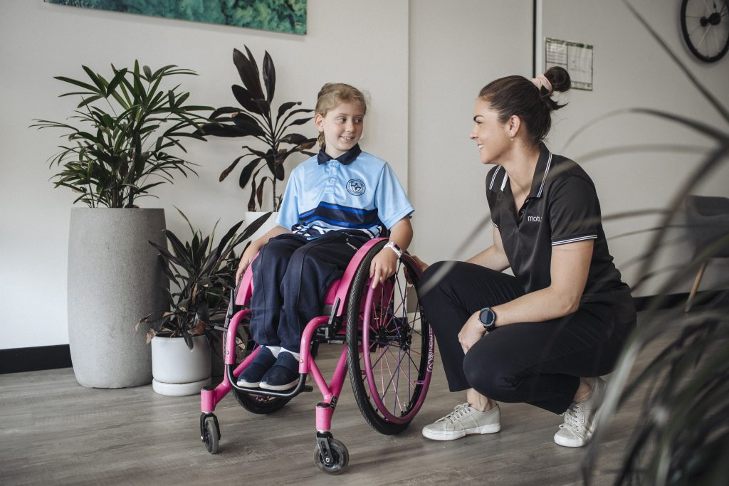 Motum Physiotherapist With Child in Wheelchair